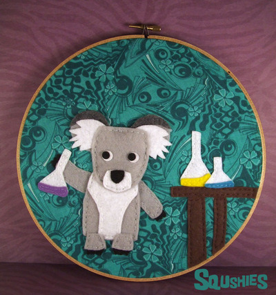 http://squshies.storenvy.com/collections/239425-wall-art/products/4111574-felt-animal-hoop-art-phoebe-the-koala